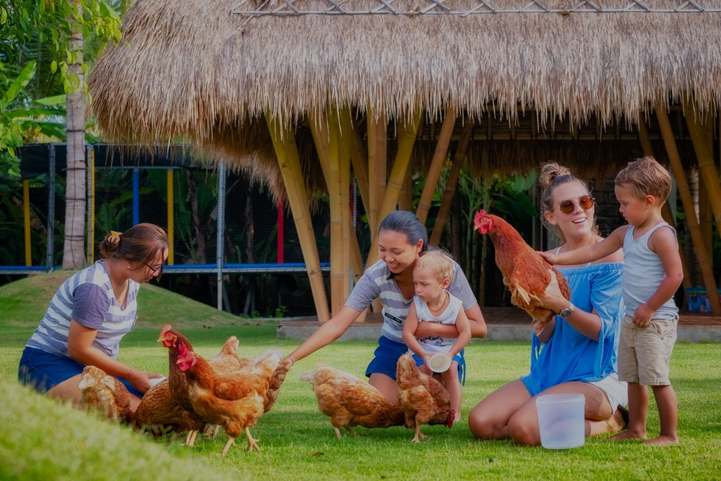 Mother and child feeding chickens at Hotel Komune